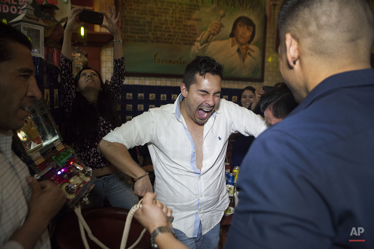 "In this Aug. 20, 2015 photo, Mario Baes screams as he holds on to an electric shock machine called ""Los toques"" inside the Salon Tenampa bar and restaurant in Garibaldi Plaza in Mexico City.  The winner of the drinking game is the one who lets go last. (AP Photo/Sofia Jaramillo)"