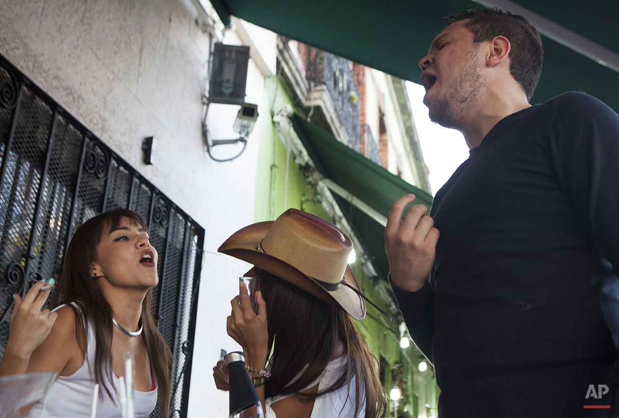 In this Aug. 19, 2015 photo, Michelle Ramirez, left, sings to mariachi music with her friends Fernanda Camerena and Adrian Roman on the patio bar at the Salon Tenampa in Garibaldi Plaza in Mexico City. With a longstanding tradition of tequila, mariachi music and dancing, the cantina is an iconic destination in Mexico City. (AP Photo/Sofia Jaramillo)