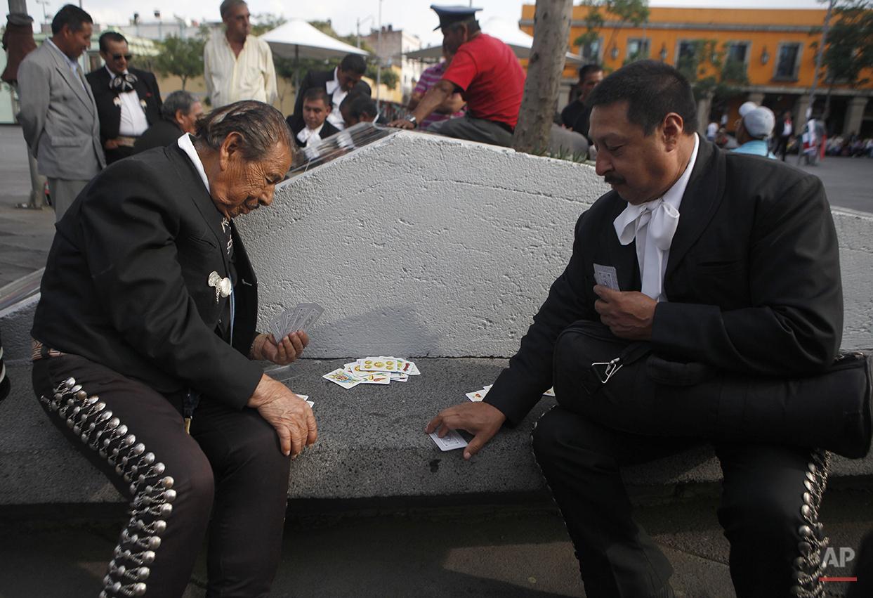 In this Aug. 8, 2015 photo, mariachi Jose Jesus, left, passes the time waiting for clients by playing cards with a fellow musician outside Salon Tenampa restaurant and bar in Garibaldi Plaza in Mexico City. To mark this year's anniversary, the restaurant has opened a small bar that overlooks the plaza, a traditional gathering spot for mariachi bands where musicians play cards or check their cellphones as they wait for potential customers. (AP Photo/Sofia Jaramillo)