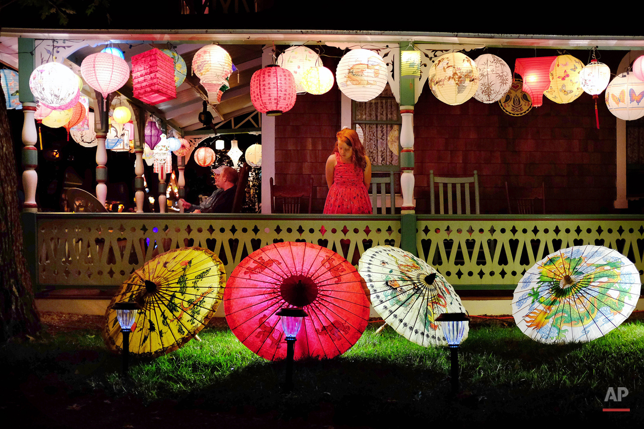 "Josie keeps an eye on her family's yard during the ""Grand Illumination Night,"" an annual tradition since 1868 in Oak Bluffs, Mass., when multitudes of paper lanterns are lit for one night decorating cottages in a historic neighborhood known as the ""Camp Ground,"" Wednesday, Aug. 20, 2014, on the island of Martha's Vineyard. (AP Photo/Jacquelyn Martin)"