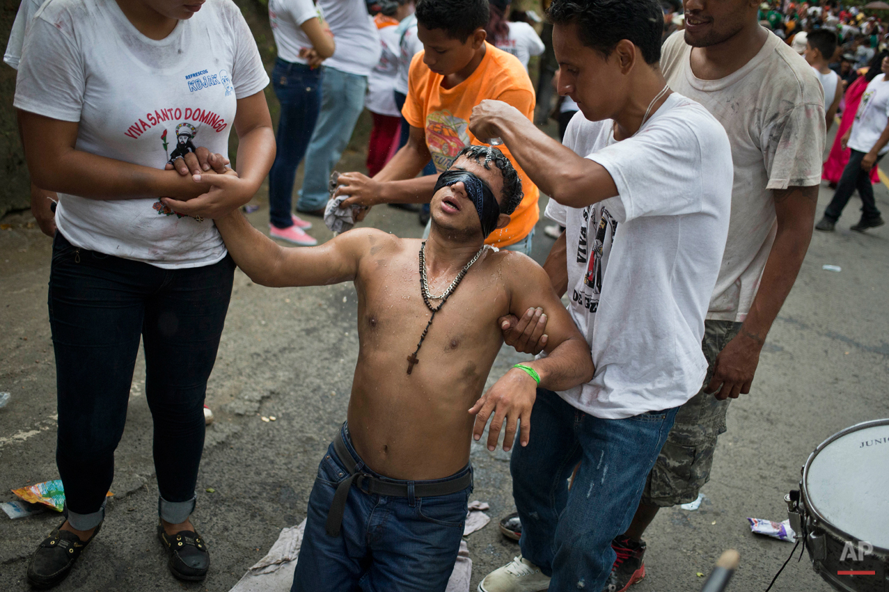 In this Aug. 10, 2015 photo, a ìpromesanteî or devotee of Managua's patron saint, Santo Domingo de Guzman, wearing a blindfold, advances on his knees towards the Las Sierritas parish church, while he is assisted relatives, as a payment for a perceived miracle performed by the saint, in Managua, Nicaragua. Devotees make the last 200 meters to the saint's altar in the Las Sierritas parish church on their knees. (AP Photo/Esteban Felix)
