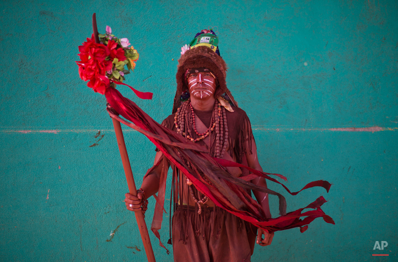 In this Aug. 4, 2015 photo, Jose Martin Tallen, 46, poses for a portrait dressed as an Indian during Managua's patron saint, Santo Domingo de Guzman's celebration, in Managua, Nicaragua. Tallen who is originally from the country's Caribbean coast says that he has been a devotee of Santo Domingo since he was six years old. (AP Photo/Esteban Felix)