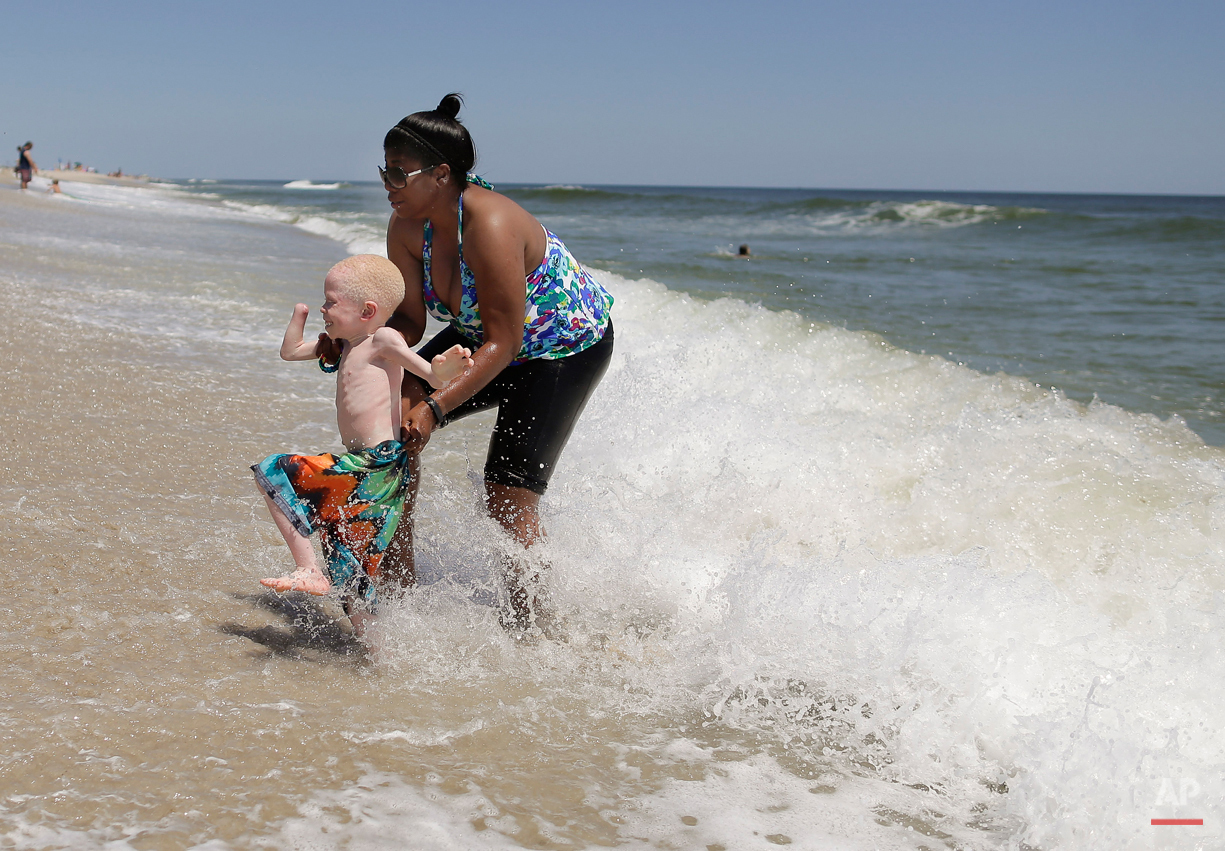 Global Medical Relief Fund assistant Monica Watson, right, helps Baraka Lusambo, 5, dart away from an approaching wave in Long Beach Island, N.J. on Wednesday, July 22, 2015. One out of every 1,400 citizens in Tanzania has albinism. Baraka was attacked and dismembered in the belief that their body parts will bring wealth. (AP Photo/Julie Jacobson)