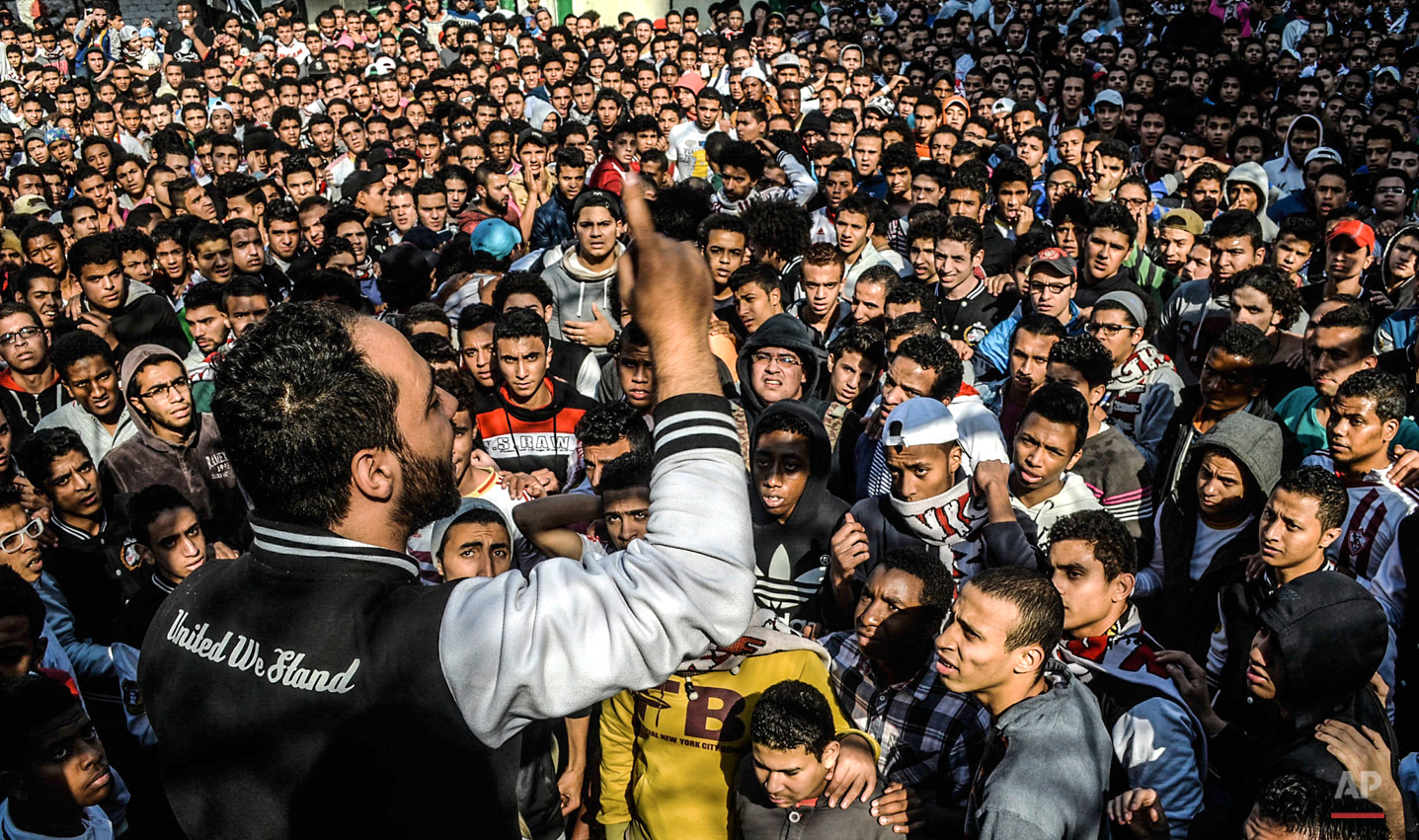 In this March 15, 2014 photo, Zamalek football clubís hardcore fan group Ultras White Knights (UWK) chant slogans during a protest against police standing guard at stadiums during all matches, in Cairo, Egypt. Often providing muscle at protests, UWK also directed demonstrators and led chants. They were considered one of the most organized movements in Egypt after the Muslim Brotherhood, which the government outlawed as a terrorist organization following the 2013 military overthrow of Islamist President Mohammed Morsi. (AP Photo/Mohammed El Raai)