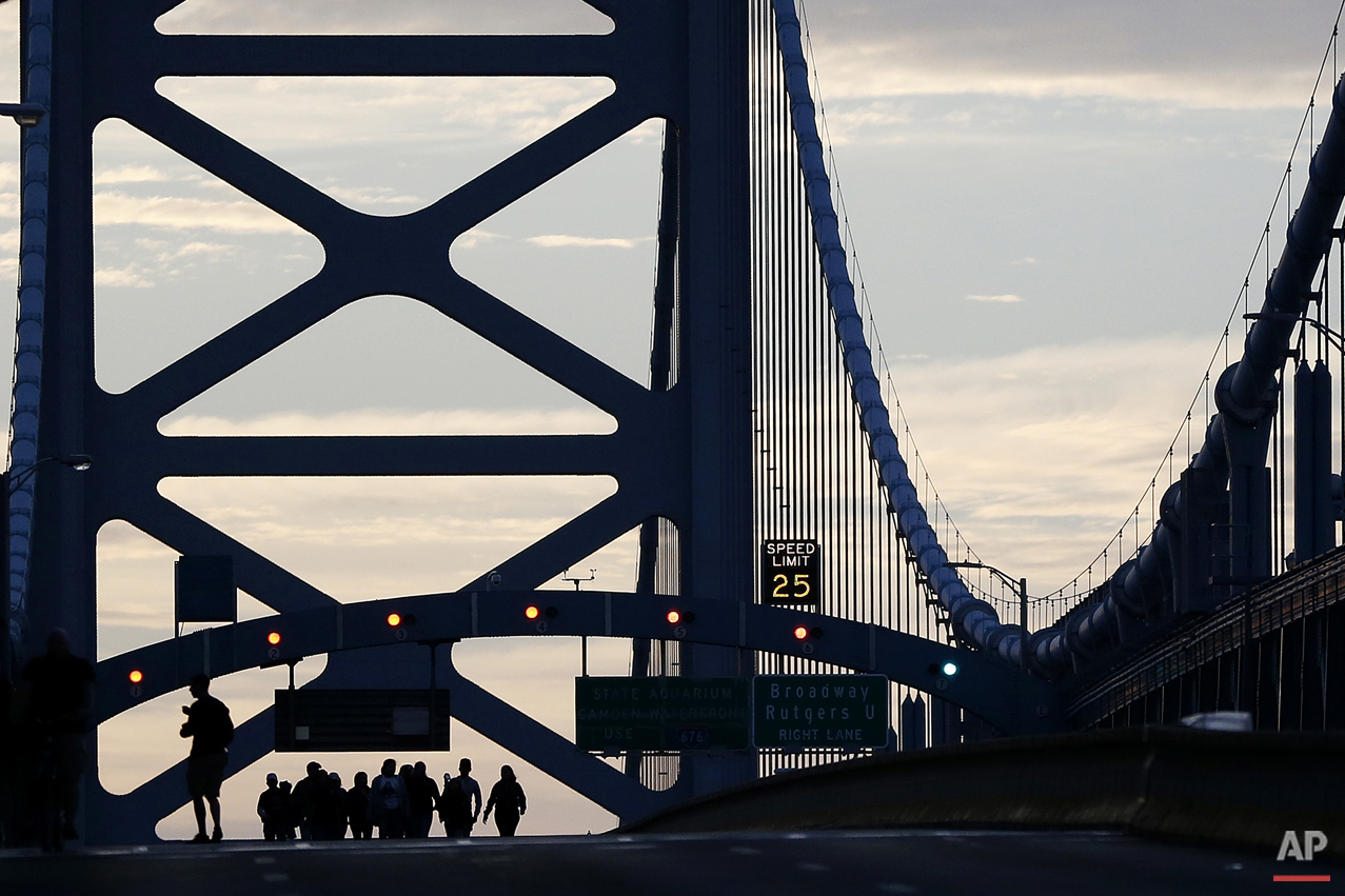 A family from Trenton, N.J., originally from Ecuador, walk over the Benjamin Franklin Bridge ahead of a Sunday Mass to be delivered by Pope Francis, Sunday, Sept. 27, 2015, in Philadelphia. Pope Francis celebrated a climactic outdoor Mass on the Benjamin Franklin Parkway Sunday before flying back to Rome. (AP Photo/Julio Cortez)