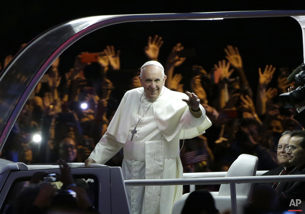Pope Francis waves as he rides in the pope mobile in the Papal Parade during the Festival of Families, Saturday, Sept. 26, 2015, in Philadelphia. (AP Photo/Matt Rourke, Pool)