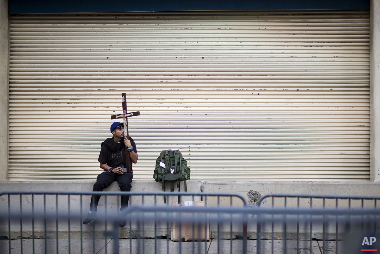 Mauro Avila, of Uvalde, Texas, sits with a cross outside a security checkpoint set up in preparation of Pope Francis' visit to Philadelphia, Friday, Sept. 25, 2015. (AP Photo/David Goldman)