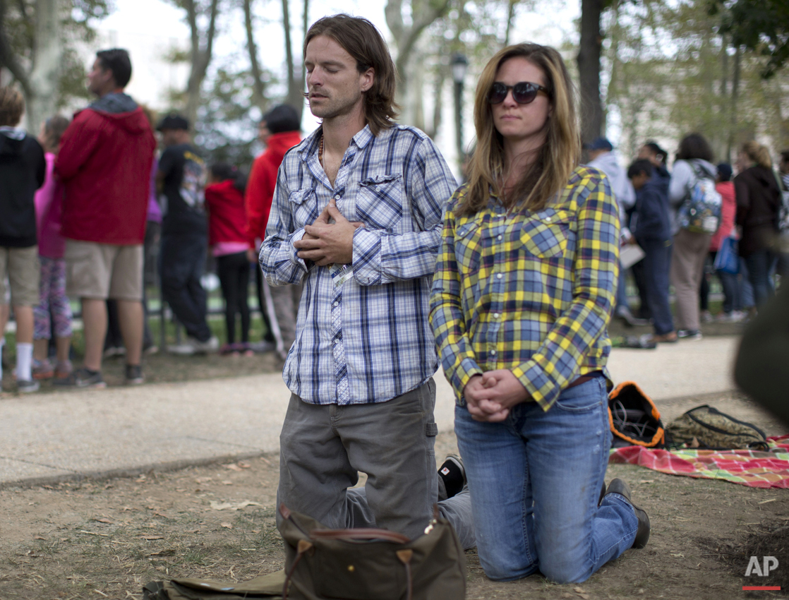 Patrick Jonynas, left, and Sommer Brooks, both from Connecticut, kneel and pray on Benjamin Franklin Parkway in Philadelphia, Sunday, Sept. 27, 2015, during the Papal Mass with Pope Francis. (AP Photo/Carolyn Kaster)