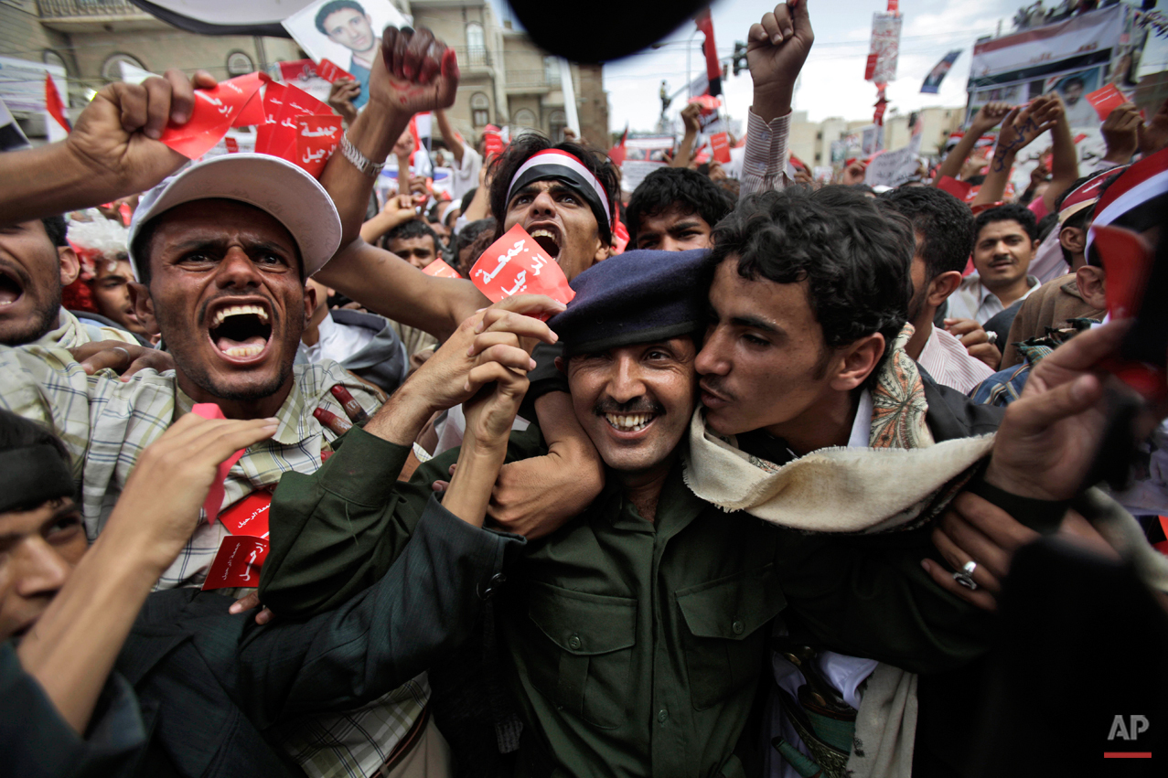 """A Yemeni army officer, center, is kissed by an anti-government protestor during a demonstration demanding the resignation of Yemeni President Ali Abdullah Saleh, in Sanaa,Yemen, Friday, March 25, 2011. Facing growing calls for his resignation, Yemen's longtime ruler told tens of thousands of supporters Friday that he's ready to leave power but he doesn't trust his opposition, whom he called """"drug dealers. Ali Abdullah Saleh spoke in a rare appearance before a cheering crowd outside his presidential palace in the Yemeni capital Friday on a day of dueling demonstrations. (AP Photo/Muhammed Muheisen)"""