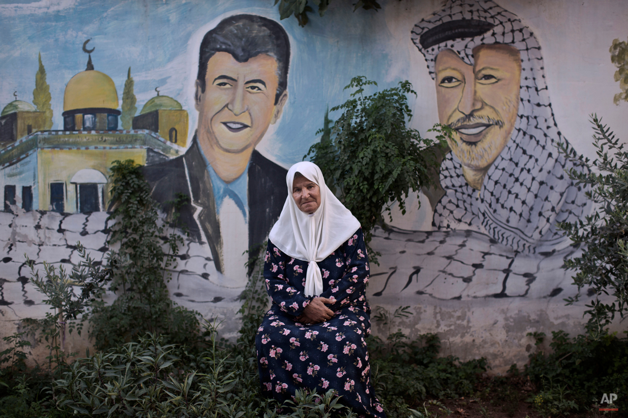 In this Tuesday, June 17, 2014 photo, Palestinian refugee Nayfeh Abu Sbaa, 70, poses for a picture in front of a mural depicting late leader Yasser Arafat, right, and her late son Akram, who was killed in 2007 by Israeli troops, in the West Bank refugee camp of Jenin. Nayfeh was 4 years old when she and 3 other members of her family were forced to leave their home in the Israeli city of Haifa. The plight of millions of refugees everywhere is marked Friday on World Refugee Day.(AP Photo/Muhammed Muheisen)