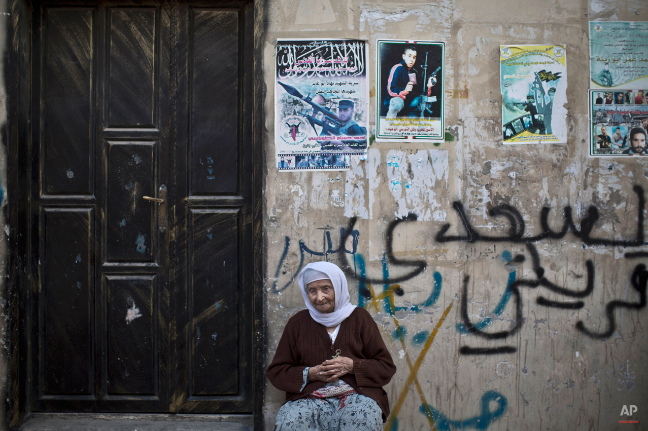 In this Tuesday, June 17, 2014 photo, Palestinian refugee Fatimah Jalamneh, 85, poses for a picture at the doorway of her home decorated with posters of militants killed by Israeli troops and others jailed in Israel in the West Bank refugee camp of Jenin. Jalamneh was in her late teens when her family fled from the village of Noures near what is now the Israeli town of Afula, along with hundreds of thousands of Palestinians fled or were forced out their homes in the Mideast war over Israel's 1948 creation. ìUntil death takes me away, my only dream is to go back to my village and sit under a tree in my home which was taken away from me and my children,î said the great-grandmother. (AP Photo/Muhammed Muheisen)