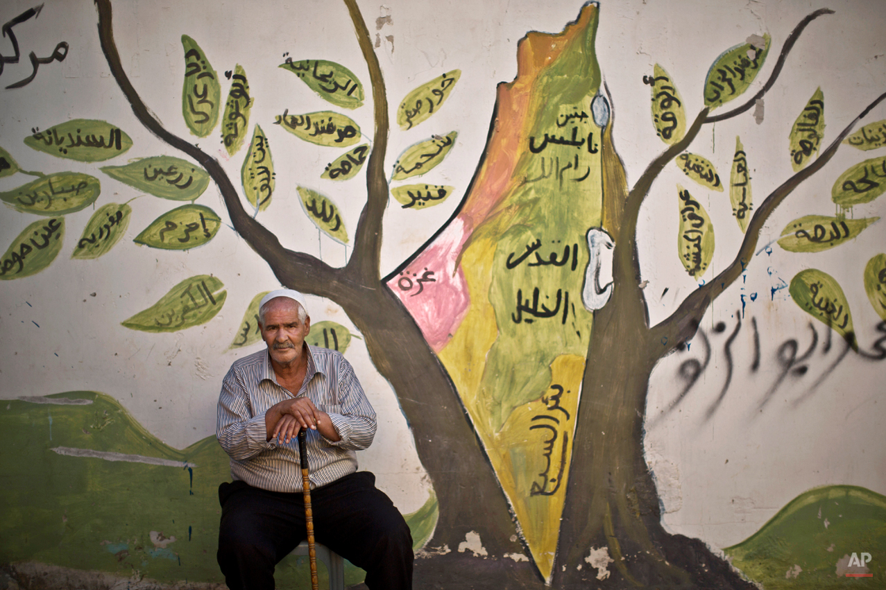 "In this Tuesday, June 17, 2014 photo, Palestinian refugee Ali Abu Jabal, 73, poses for a picture in front of a wall painted with a mural depicting the holy land, in the West Bank refugee camp of Jenin. The man was 7 years old when he and his parents were forced to leave their home in the Israeli city of Haifa during what the Palestinians call the ""Nakba,"" or ìcatastropheî referring to their uprooting in the war over Israel's 1948 creation.(AP Photo/Muhammed Muheisen)"