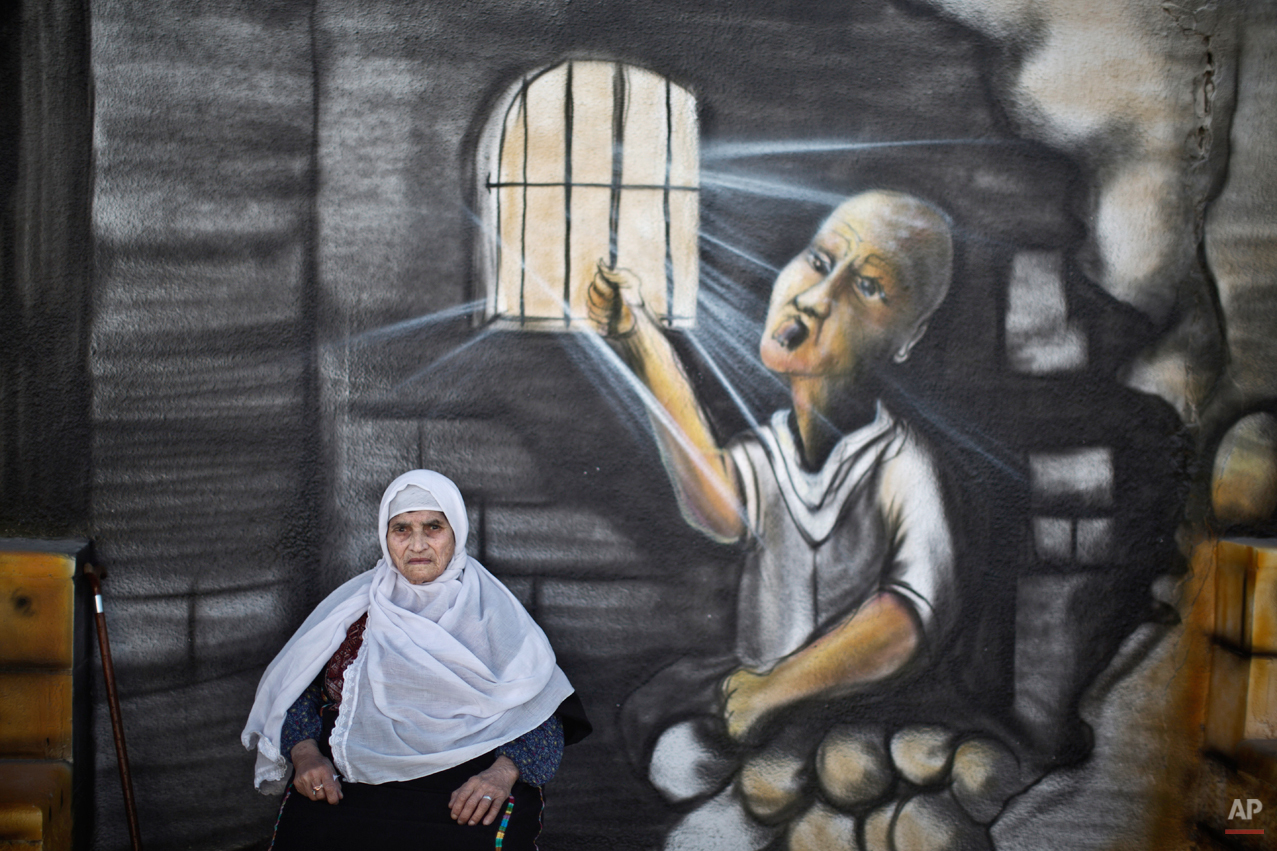In this Sunday, June 15, 2014 photo, Palestinian refugee Sabhah Abu Latifah, 85,  poses for a picture in front of a wall painted with a mural depicting prisoners jailed in Israel in Kalandia refugee camp between Jerusalem and the West Bank city of Ramallah, were she has lived with her family since they fled during the war over Israel's 1948 creation. She was 19 years old.(AP Photo/Muhammed Muheisen)