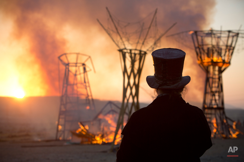 In this photo taken Saturday, June 7, 2014, a man looks at a wooden sculpture that was set on fire during Israelís first Midburn festival, modeled after the popular Burning Man festival held annually in the Black Rock Desert of Nevada, in the desert near the Israeli kibbutz of Sde Boker. Some 3,000 people set up a colorful encampment in the dusty moonscape, swinging from hoops by day and burning giant wooden sculptures by night. (AP Photo/Oded Balilty)