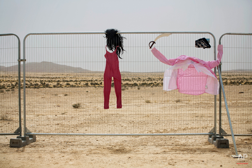In this photo taken Wednesday, June 4, 2014, costumes hang on a fence at the first Israelís Midburn festival, modeled after the popular Burning Man festival held annually in the Black Rock Desert of Nevada, in the desert near the Israeli kibbutz of Sde Boker. The festival took place a few miles southwest of the desert gravesite of Israelís founding father, David Ben-Gurion, who dreamed of making the Negev desert bloom _ though he probably didnít envisioned it blossoming with hula hoops and pyrotechnics. At the end, participants were told to remove their own trash and leave the desert without a trace.(AP Photo/Oded Balilty)