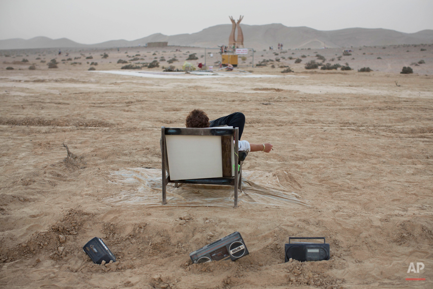In this photo taken Wednesday, June 4, 2014, an Israeli man rests on a couch during Israelís first Midburn festival, modeled after the popular Burning Man festival held annually in the Black Rock Desert of Nevada, in the desert near the Israeli kibbutz of Sde Boker. Some 3,000 people set up a colorful encampment in the dusty moonscape, swinging from hoops by day and burning giant wooden sculptures by night. (AP Photo/Oded Balilty)