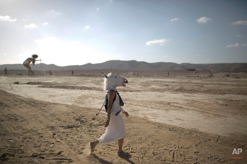 """In this photo taken Friday, June 6, 2014, An Israeli woman wears a unicorn mask as she walks in the playa during Israelís first Midburn festival, modeled after the popular Burning Man festival held annually in the Black Rock Desert of Nevada, in the desert near the Israeli kibbutz of Sde Boker. Some 3,000 people set up a colorful encampment in the dusty moonscape, swinging from hoops by day and burning giant wooden sculptures by night. For five days, participants mostly Israelis created a temporary city dedicated to creativity, communal living, and what the festival calls ìradical self-expression."""" (AP Photo/Oded Balilty)"""