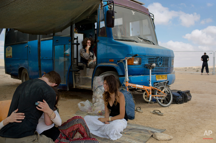 """In this photo taken Saturday, June 7, 2014, Israelis sits under the shade during Israelís first Midburn festival, modeled after the popular Burning Man festival held annually in the Black Rock Desert of Nevada, in the desert near the Israeli kibbutz of Sde Boker. For five days, participants, mostly Israelis ,created a temporary city dedicated to creativity, communal living, and what the festival calls ìradical self-expression."""" (AP Photo/Oded Balilty)"""