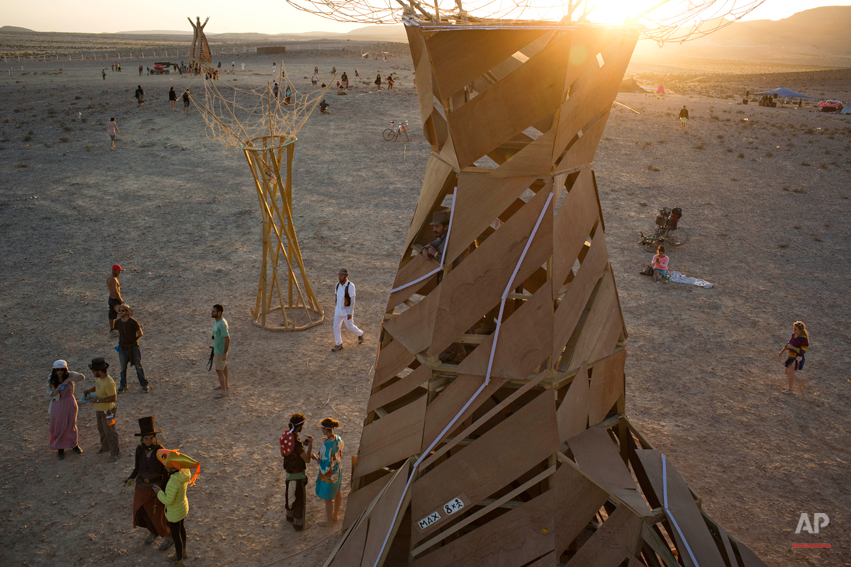 In this photo taken Friday, June 6, 2014, people, mostly Israelis, walk in the playa during Israelís first Midburn festival, modeled after the popular Burning Man festival held annually in the Black Rock Desert of Nevada, in the desert near the Israeli kibbutz of Sde Boker. Some 3,000 people set up a colorful encampment in the dusty moonscape, swinging from hoops by day and burning giant wooden sculptures by night. At the end, participants were told to remove their own trash and leave the desert without a trace.(AP Photo/Oded Balilty)