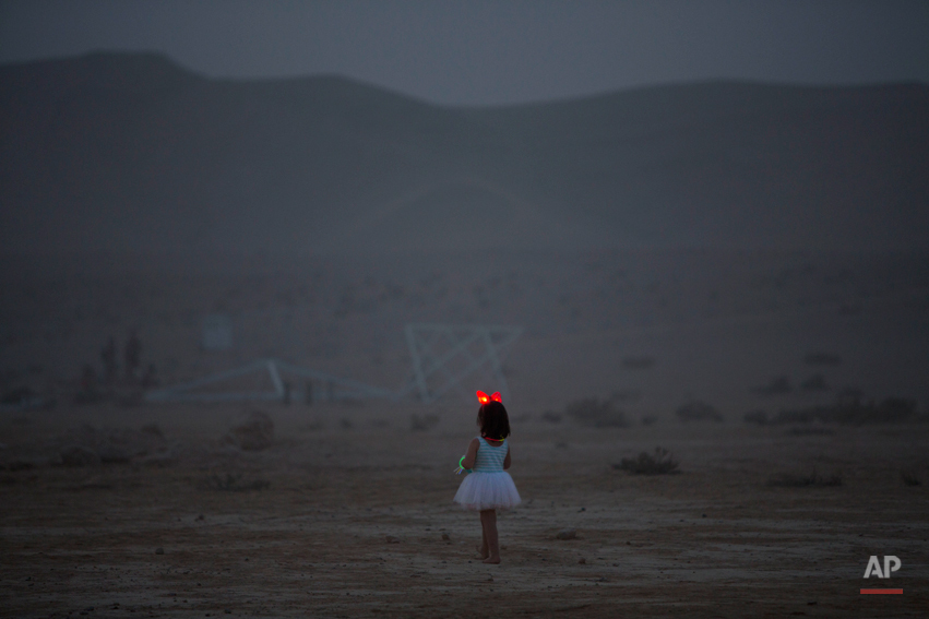 In this photo taken Wednesday, June 4, 2014, a young Israeli girl walks in the playa during Israelís first Midburn festival, modeled after the popular Burning Man festival held annually in the Black Rock Desert of Nevada, in the desert near the Israeli kibbutz of Sde Boker. Some came costumed in cape or corset. Others, from babies to grandparents, went nude. Participants brought their own food and water, and shared with others. The only thing on sale was ice because of the scorching heat. (AP Photo/Oded Balilty)
