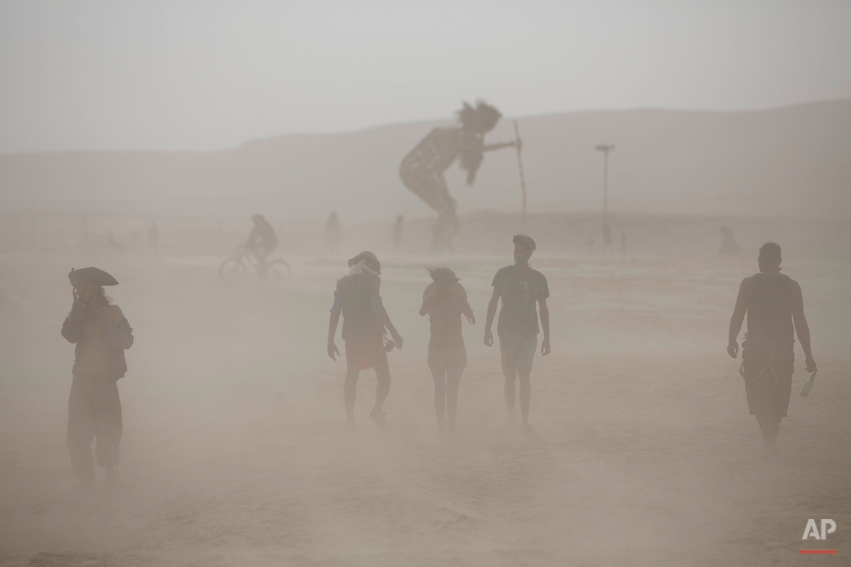 """In this photo taken Thursday, June 5, 2014, people walk in the dusty playa during Israelís first Midburn festival, modeled after the popular Burning Man festival held annually in the Black Rock Desert of Nevada, in the desert near the Israeli kibbutz of Sde Boker. For five days, participants, mostly Israelis, created a temporary city dedicated to creativity, communal living, and what the festival calls ìradical self-expression."""" (AP Photo/Oded Balilty)"""