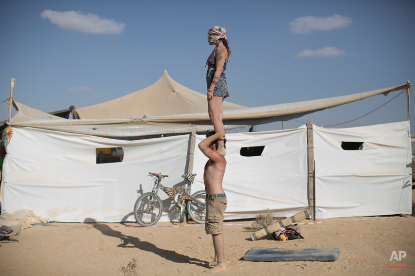 """In this photo taken Friday, June 6, 2014, Israeli acrobats perform during Israelís first Midburn festival, modeled after the popular Burning Man festival held annually in the Black Rock Desert of Nevada, in the desert near the Israeli kibbutz of Sde Boker. Some 3,000 people set up a colorful encampment in the dusty moonscape, swinging from hoops by day and burning giant wooden sculptures by night. For five days, participants mostly Israelis created a temporary city dedicated to creativity, communal living, and what the festival calls ìradical self-expression"""". (AP Photo/Oded Balilty)"""