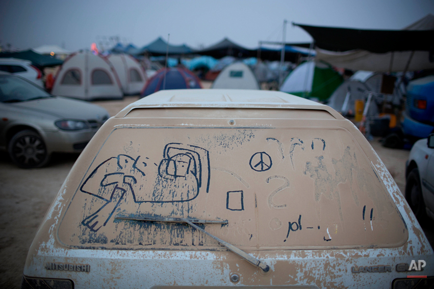 In this photo taken Wednesday, June 4, 2014, hand writing and doodles adorn a dusty car during Israelís first Midburn festival, modeled after the popular Burning Man festival held annually in the Black Rock Desert of Nevada, in the desert near the Israeli kibbutz of Sde Boker. For five days, participants _ mostly Israelis _ created a temporary city dedicated to creativity, communal living and what the festival calls ìradical self-expression.î (AP Photo/Oded Balilty)