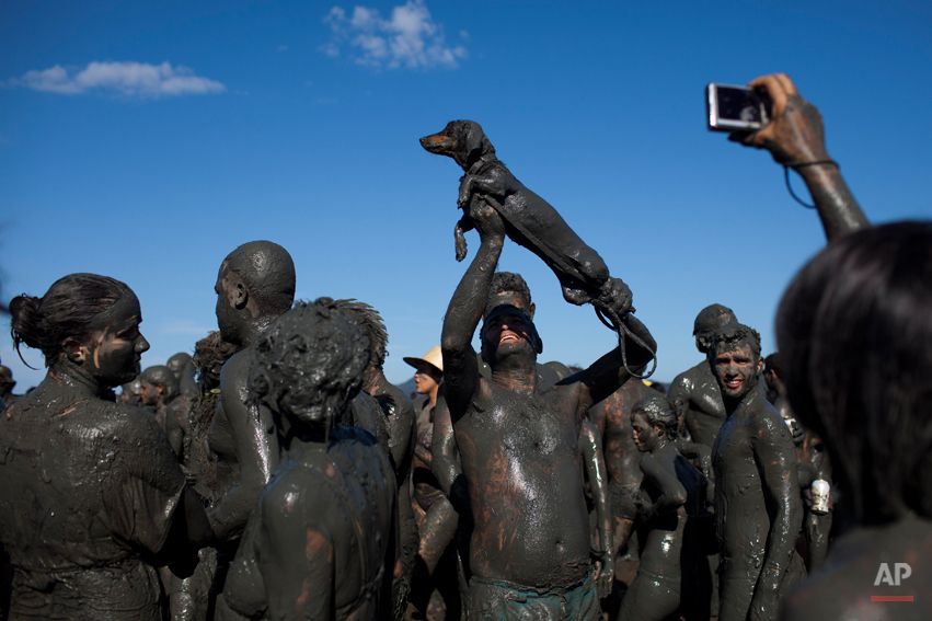 """A man covered in mud holds up his mud covered dog as another reveler takes a picture during the """"Bloco da Lama"""" or """"Mud Block"""" carnival parade in Parati, Brazil, Saturday Feb. 18, 2012. (AP Photo/Felipe Dana)"""