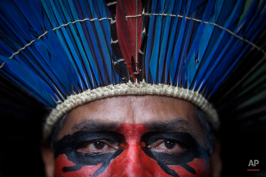 An indigenous man wearing face paint and a headdress stands inside the abandoned old Indian museum in Rio de Janeiro, Brazil, Thursday, March 21, 2013. Brazilian Federal Court ruled that indigenous people who have been occupying the building since 2006 have to leave the area because it is next to the Maracana stadium, which will be the site of the final match of the 2014 World Cup soccer tournament and the opening and closing ceremonies of the 2016 Olympic games. Authorities say the compound must go as the area around the stadium is being transformed into a shopping and sports entertainment hub. (AP Photo/Felipe Dana)