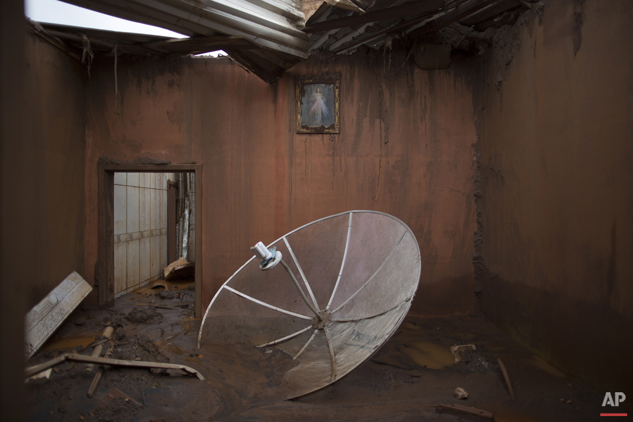 In this Nov. 23, 2015 photo, a satellite dish sits amid debris in a home destroyed when dams of an iron ore mine burst in early November, causing a mudslide, in the village of Bento Rodrigues, Brazil. The village, in the central state of Minas Gerais, was home to about 600 people until Nov. 5, when the dam burst, unleashing a tsunami of mud that swept away nearly everything in its path, flattening houses, uprooting trees and tossing cars asunder. (AP Photo/Leo Correa)