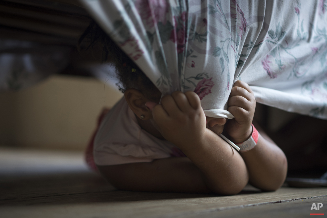 Five-year-old Nicole eats a lollipop as she playfully pulls a bed sheet over her eyes, at a hotel housing people displaced from a dam failure, in Mariana, in the Brazilian state of Minas Gerais, Monday, Nov. 9, 2015. Nicole's home was destroyed Thursday when two dams at an iron ore mine flooded Bento Rodrigues, a village in southeastern Brazil. Gov. Fernando Pimentel said it was still not known what triggered the failure of dams at the Samarco mine, which sent viscous red mud, water and debris flooding into Bento Rodrigues, flattening all but a handful of buildings. (AP Photo/Felipe Dana)