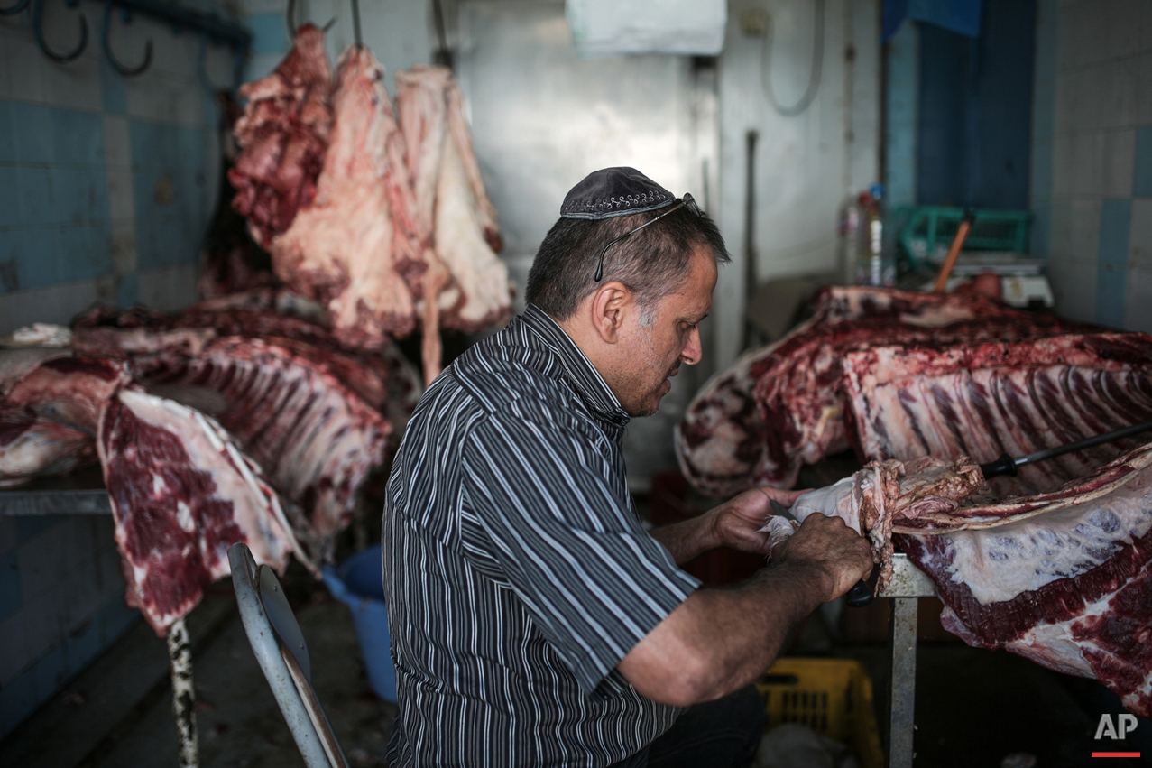 "In this Wednesday, Oct. 28, 2015 photo, Char Haddad, 45, prepares meat in his kosher slaughterhouse at Hara Kbira, the main Jewish neighbourhood on the Island of Djerba, southern Tunisia. The surrounding streets include a kosher butcher, a bakery that sells a traditional tuna-filled pastry known as ""brik"" and schools that teach lessons in Hebrew, French and Arabic. (AP Photo/Mosa'ab Elshamy)"