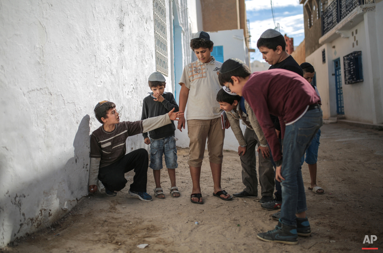 In this Friday, Oct. 30, 2015 photo, boys play with marbles outside their school at Hara Kbira, the main Jewish neighbourhood in the Island of Djerba, southern Tunisia. The Jewish community on the resort island of Djerba traces its roots all the way back to Babylonian exile of 586 B.C., and is one of the few communities of its kind to have survived the turmoil around the creation of Israel, when more than 800,000 Jews across the Arab world either emigrated or were driven from their homes. (AP Photo/Mosa'ab Elshamy)