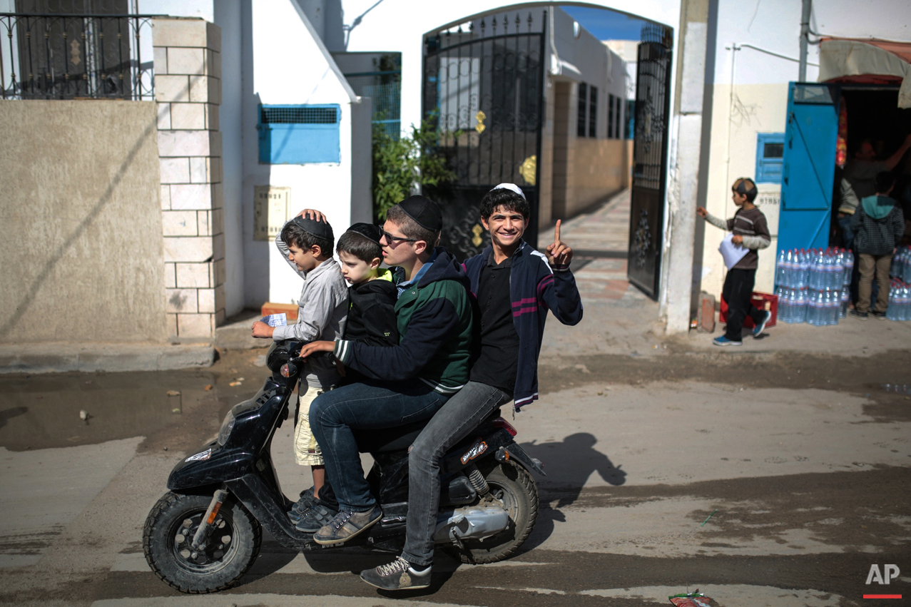In this Friday, Oct. 30, 2015 photo, a boy gestures to the camera as he and his relatives leave school at Hara Kbira, the main Jewish neighbourhood on the Island of Djerba, southern Tunisia. Tunisia's Jewish population has dwindled from 100,000 in 1956, when the country won independence from France, to less than 1,500, mainly as a result of emigration to France and Israel. But unlike in much of the rest of the Arab world, Tunisian Jews have seen little direct persecution and have only rarely been targeted by extremists. (AP Photo/Mosa'ab Elshamy)