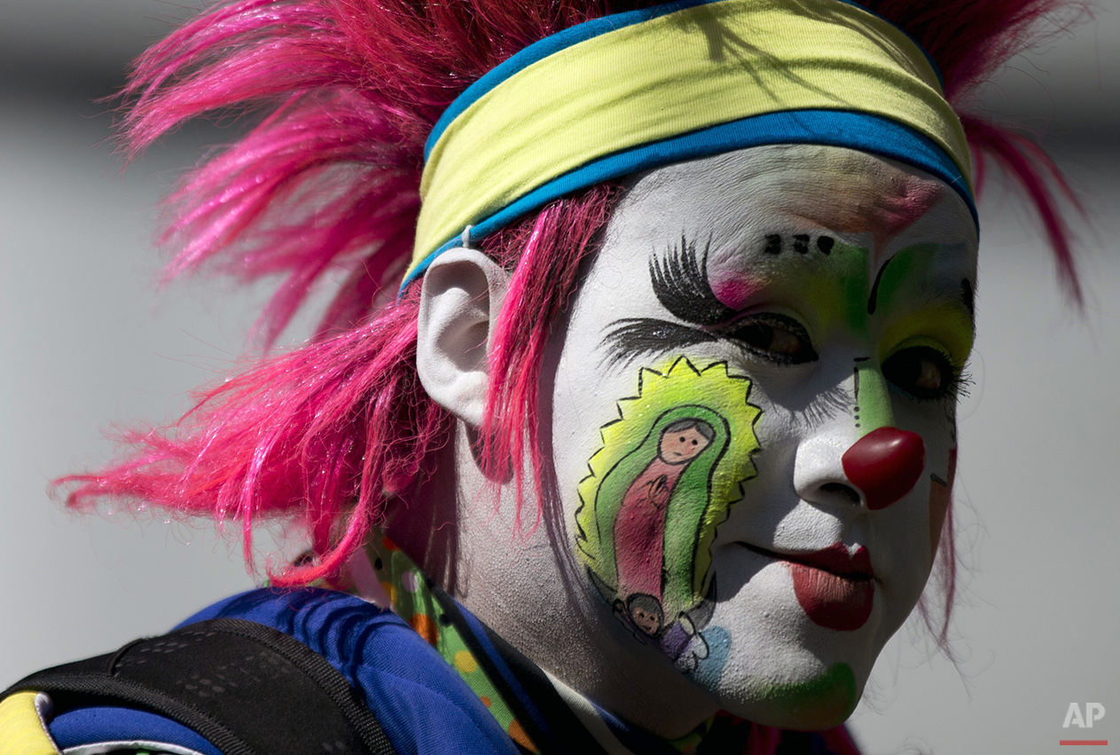 A clown with his cheek painted with an image of the Virgin of Guadalupe walks in a procession toward the Basilica of Our Lady of Guadalupe in Mexico City, Monday, Dec. 14, 2015. Hundreds of clowns belonging to various clown associations made their annual pilgrimage to the Basilica on Monday to pay their respects to the Virgin of Guadalupe, Mexico's patron saint. (AP Photo/Rebecca Blackwell)