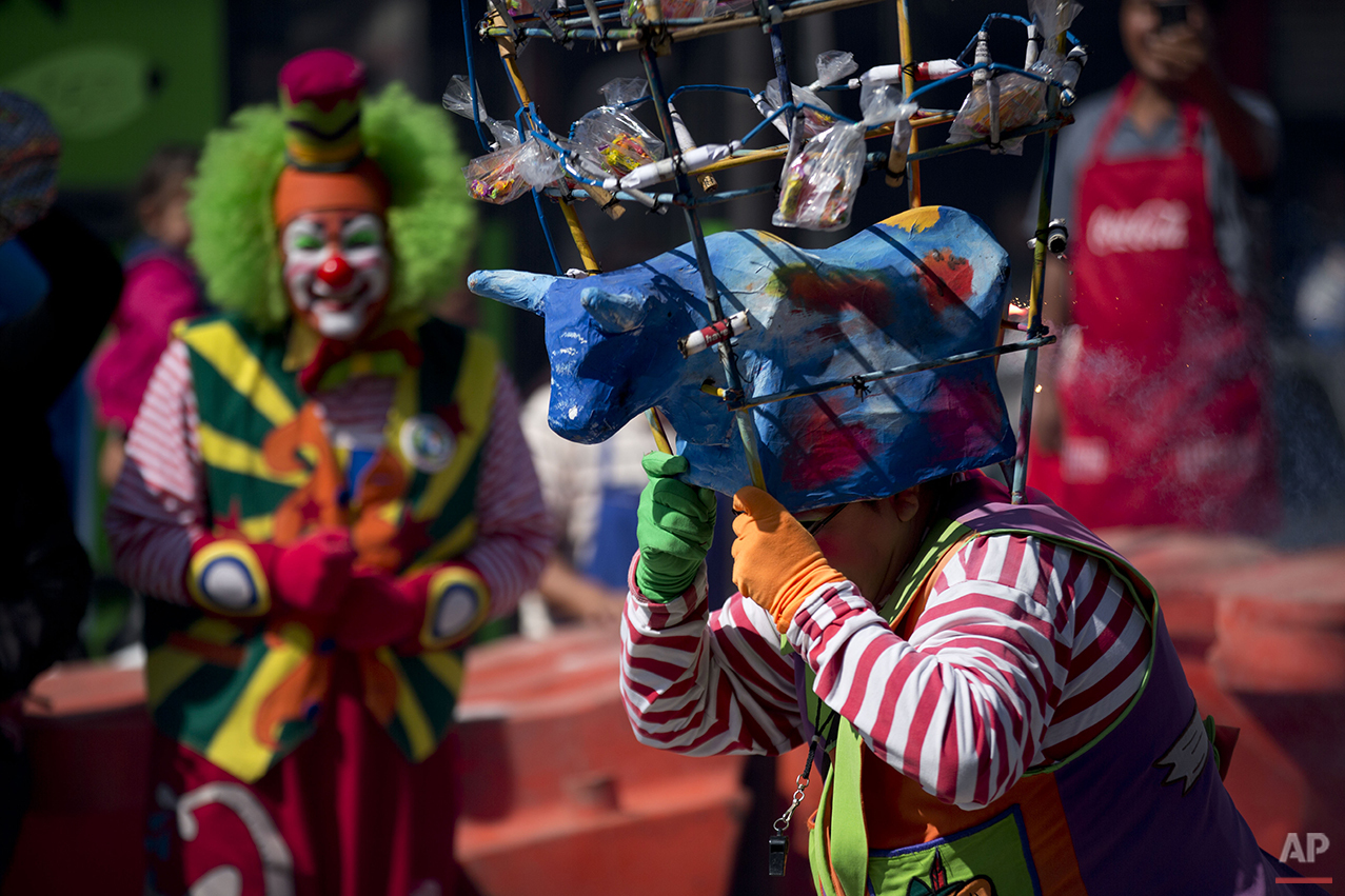 A clown runs carrying a bull headdress adorned with firecrackers, as clowns march in procession toward the Basilica of Our Lady of Guadalupe in Mexico City, Monday, Dec. 14, 2015. Hundreds of clowns belonging to various clown associations made their annual pilgrimage to the Basilica on Monday to pay their respects to the Virgin of Guadalupe, Mexico's patron saint. (AP Photo/Rebecca Blackwell)