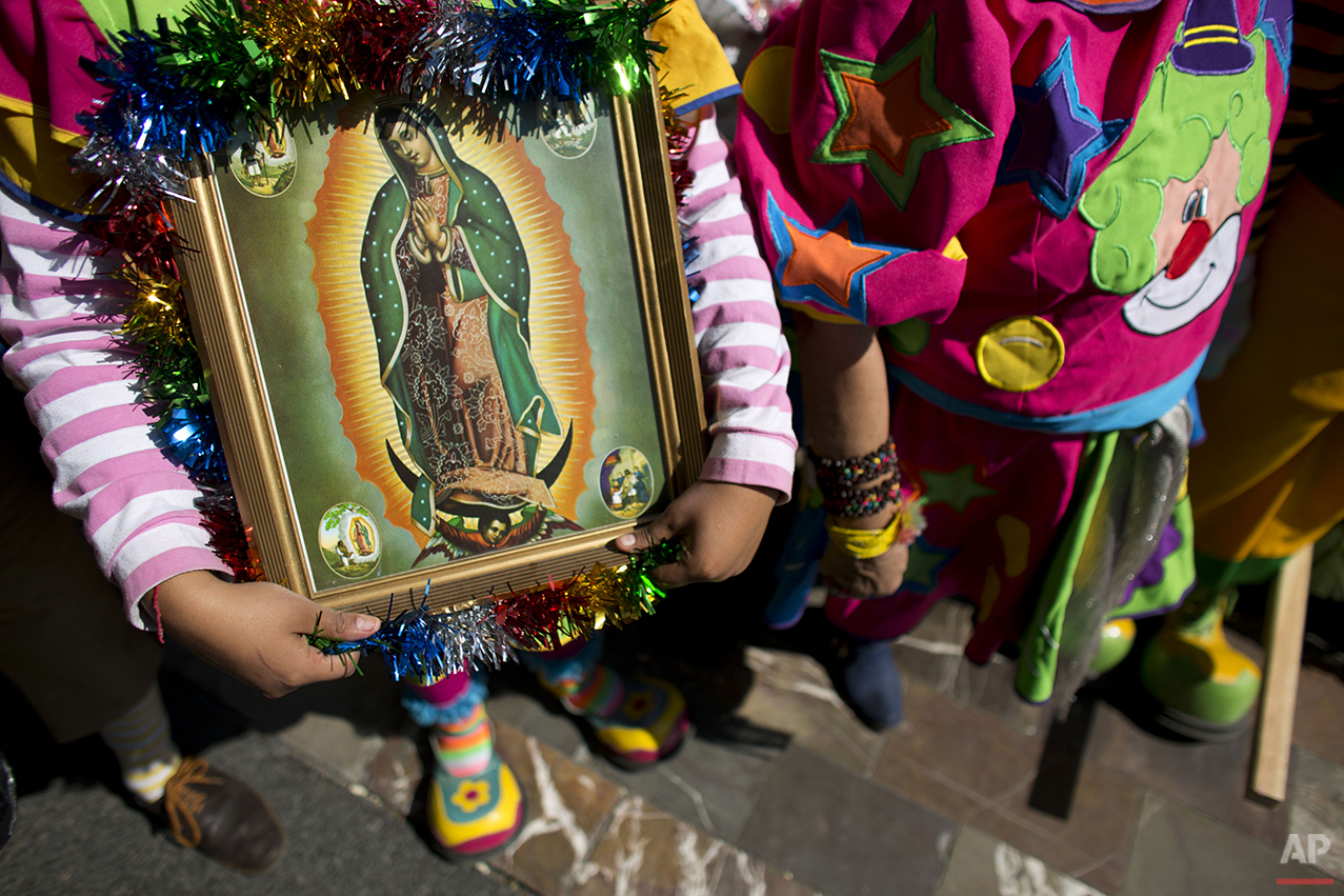 A clown carries a picture of the Virgin of Guadalupe, as she waits to enter the Basilica of Our Lady of Guadalupe in Mexico City, Monday, Dec. 14, 2015. Hundreds of clowns belonging to various clown associations made their annual pilgrimage to the Basilica on Monday to pay their respects to the Virgin of Guadalupe, Mexico's patron saint. (AP Photo/Rebecca Blackwell)