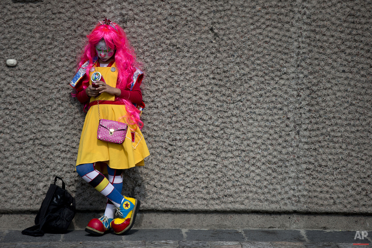 A clown checks her phone as she waits outside the Basilica of Our Lady of Guadalupe, in Mexico City, Monday, Dec. 14, 2015. Hundreds of clowns belonging to various clown associations made their annual pilgrimage to the Basilica on Monday to pay their respects to the Virgin of Guadalupe, Mexico's patron saint. (AP Photo/Rebecca Blackwell)