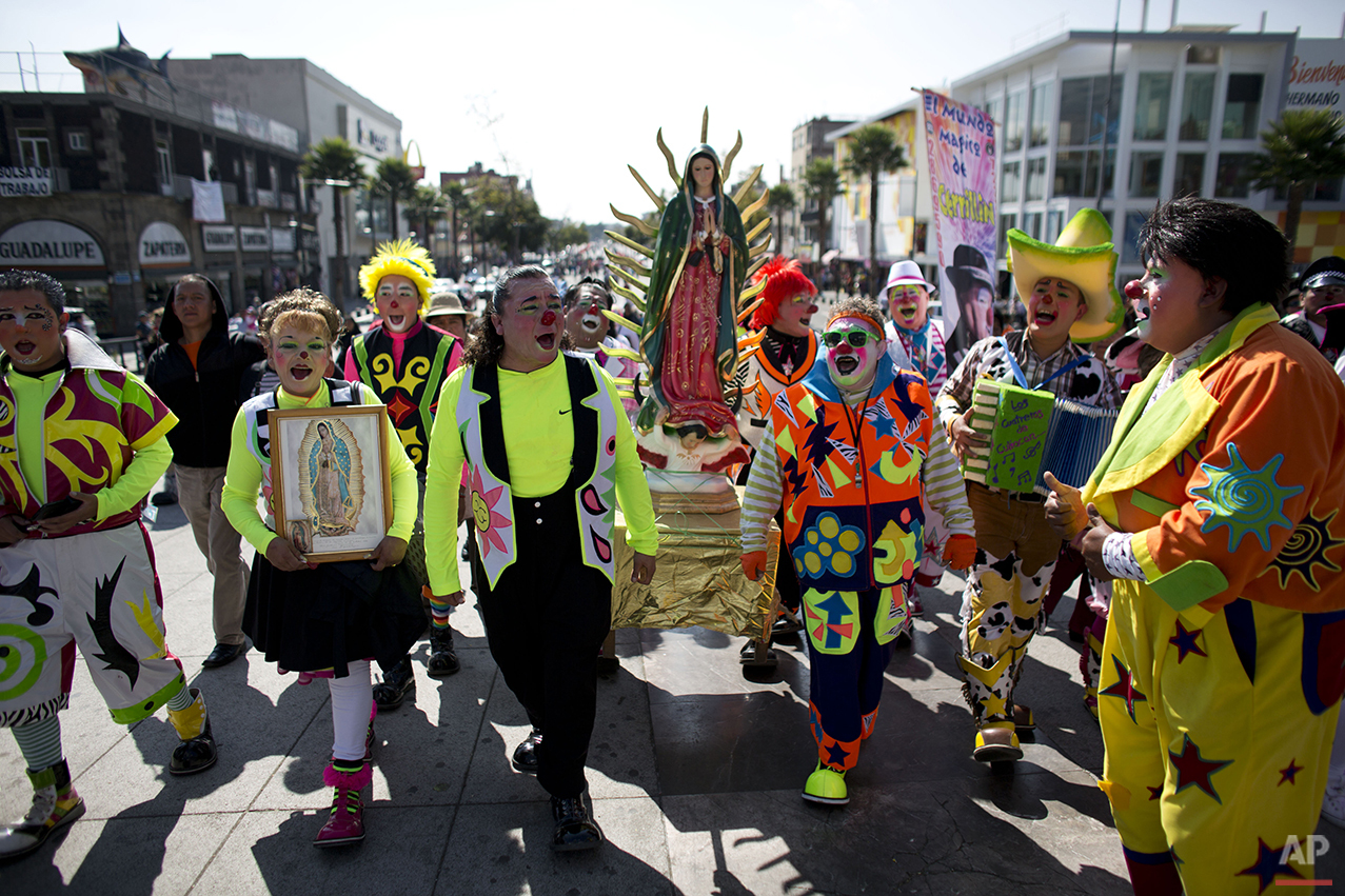 Clowns carry a statue of the Virgin of Guadalupe, as they arrive at the Basilica of Our Lady of Guadalupe in Mexico City, Monday, Dec. 14, 2015. Hundreds of clowns belonging to various clown associations made their annual pilgrimage to the Basilica on Monday to pay their respects to the Virgin of Guadalupe, Mexico's patron saint. (AP Photo/Rebecca Blackwell)