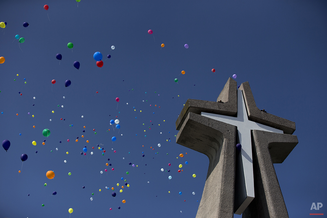 Balloons released by clowns rise over the cross at the Basilica of Our Lady of Guadalupe in Mexico City, Monday, Dec. 14, 2015. Hundreds of clowns belonging to various clown associations made their annual pilgrimage to the Basilica on Monday to pay their respects to the Virgin of Guadalupe, Mexico's patron saint. (AP Photo/Rebecca Blackwell)
