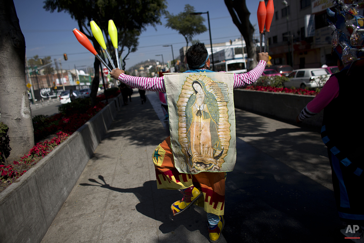 A clown wears an image of the Virgin of Guadalupe as he walks in procession toward the Basilica of Our Lady of Guadalupe in Mexico City, Monday, Dec. 14, 2015. Hundreds of clowns belonging to various clown associations made their annual pilgrimage to the Basilica on Monday to pay their respects to the Virgin of Guadalupe, Mexico's patron saint. (AP Photo/Rebecca Blackwell)