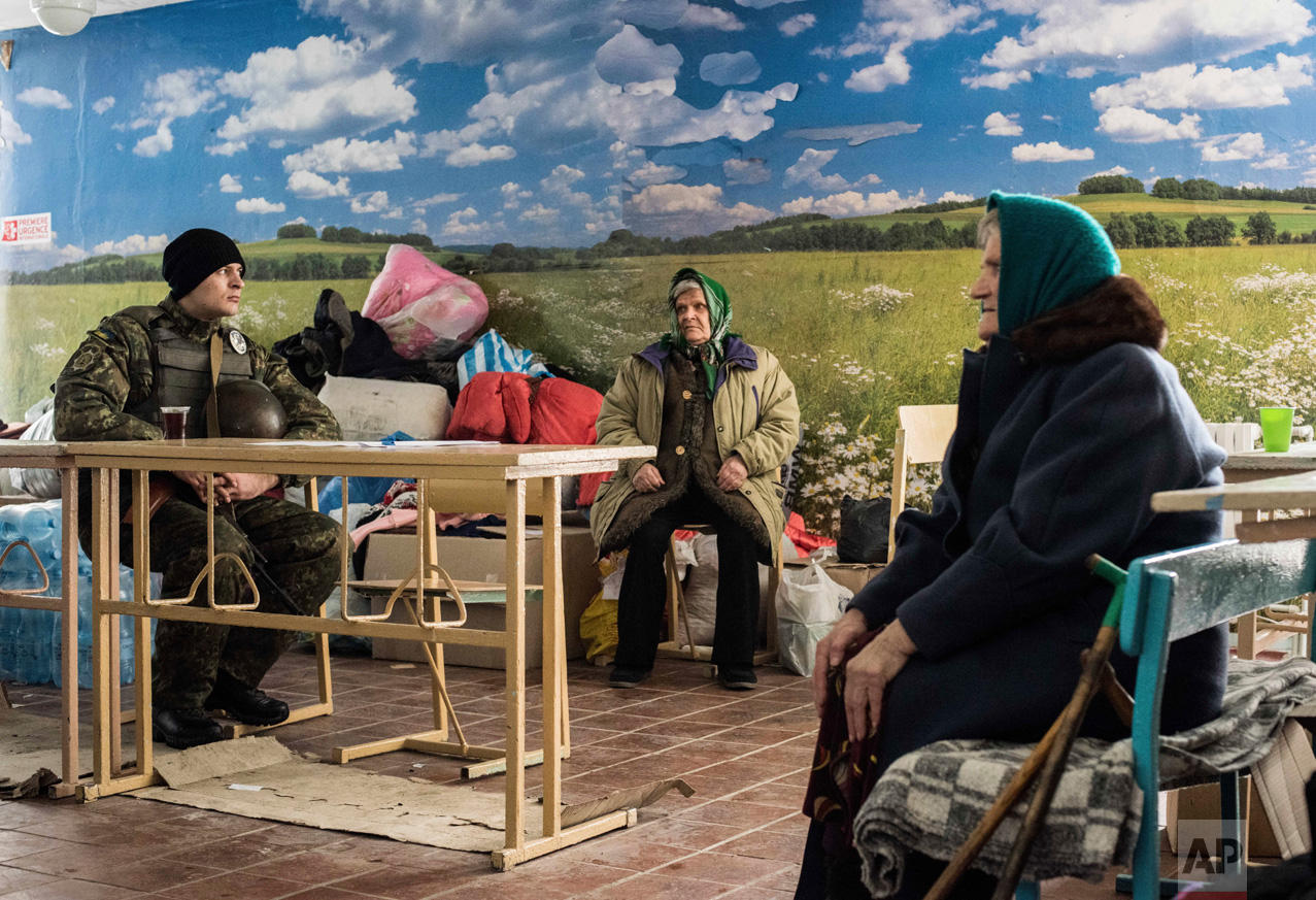 A Ukrainian soldier, left, sits next to two elderly women waiting for humanitarian aid in Avdiivka, eastern Ukraine, Sunday, Feb. 5, 2017. A sharp escalation in fighting between Ukrainian troops and Russia-backed rebels over the past week has killed at least 33 people, centering on Avdiivka, a government-held town just north of rebel-controlled Donetsk. (AP Photo/Evgeniy Maloletka)