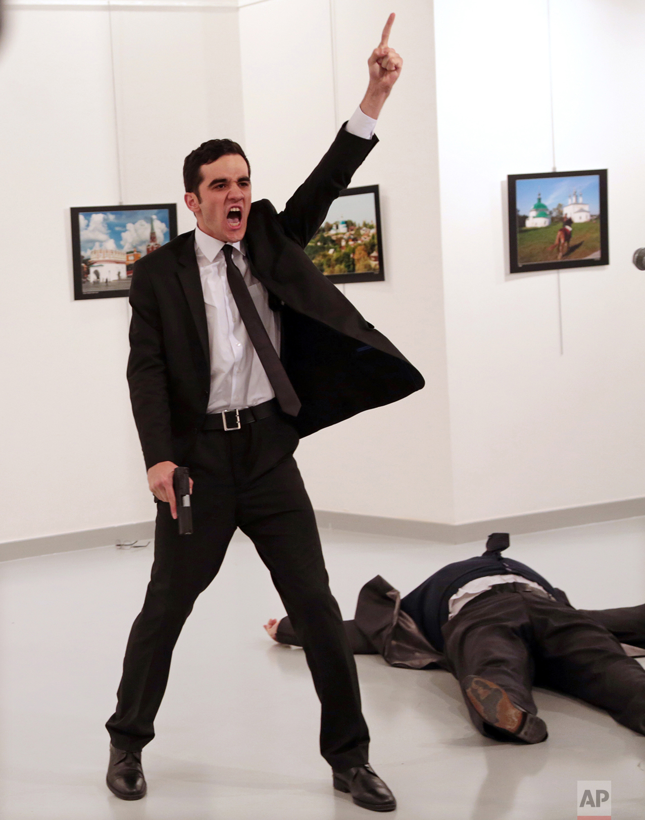 """Mevlut Mert Altintas shouts after shooting Andrei Karlov, right, the Russian ambassador to Turkey, at an art gallery in Ankara, Turkey, Monday, Dec. 19, 2016. Associated Press photographer Burhan Ozbilici won the 2017 World Press Photo competition Monday Feb. 13, 2017 for the image. It was part of a series titled """"An Assassination in Turkey"""" which also won the Spot News - Stories category, captured in the moments before and after Altintas, an off-duty policeman, drew a handgun and shot Karlov at a photo exhibition.(AP Photo/Burhan Ozbilici)"""