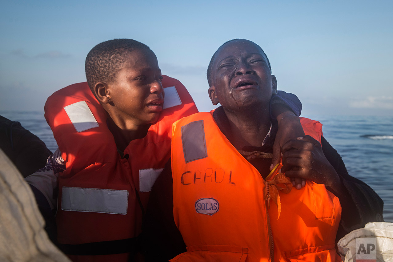 In this Thursday, July 28, 2016 photo, by photographer Santi Palacios which won second prize in the General News, Singles, category of the World Press Photo contest shows an 11-year-old girl from Nigeria, right, who said her mother died in Libya, crying next to her 10-year-old brother aboard an NGO rescue boat, on 28 July 2016. The children had sailed for hours in an overcrowded rubber boat with other refugees during a rescue operation on the Mediterranean Sea, about 23 kilometers north of Sabratha, Libya. (AP Photo/Santi Palacios)