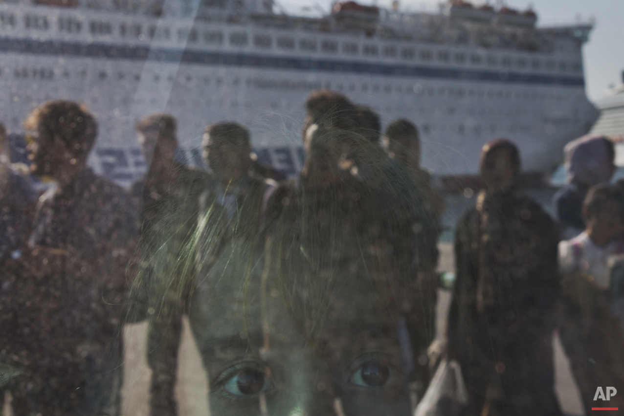 A child looks out from a window of a bus upon arriving by a ferry from the Greek island of Lesbos at the Athens' port of Piraeus on Thursday, Oct. 15, 2015. The international Organization for Migration said than more than 593,000 people have crossed into Europe  this year — of which 453,000 traveled from Turkey to Greece, which has faced a massive influx of people from Syria.(AP Photo/Petros Giannakouris)