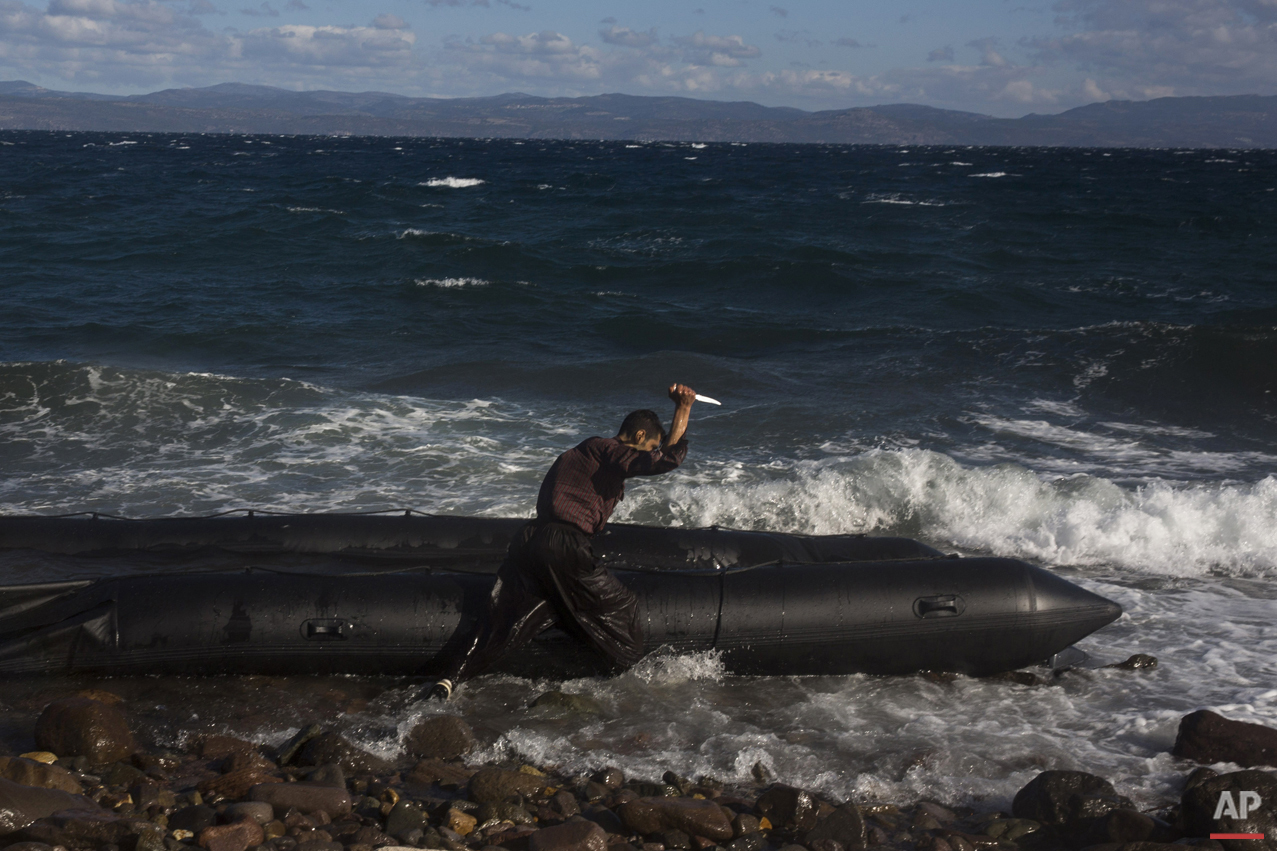 Afghan migrant uses a knife to puncture the dinghy in which he crossed with others from Turkey to the Greek island of Lesbos, Wednesday, Oct. 28, 2015. (AP Photo/Santi Palacios)
