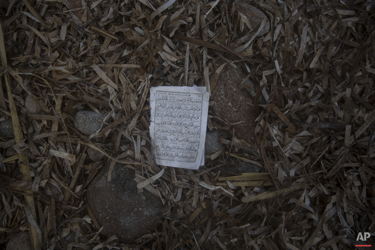 A page form the Quran lies on the beach in the Greek island of Lesbos, where hundreds of refugees are arriving every day from the Turkish coast, Friday, Oct. 2, 2015.  (AP Photo/Santi Palacios)