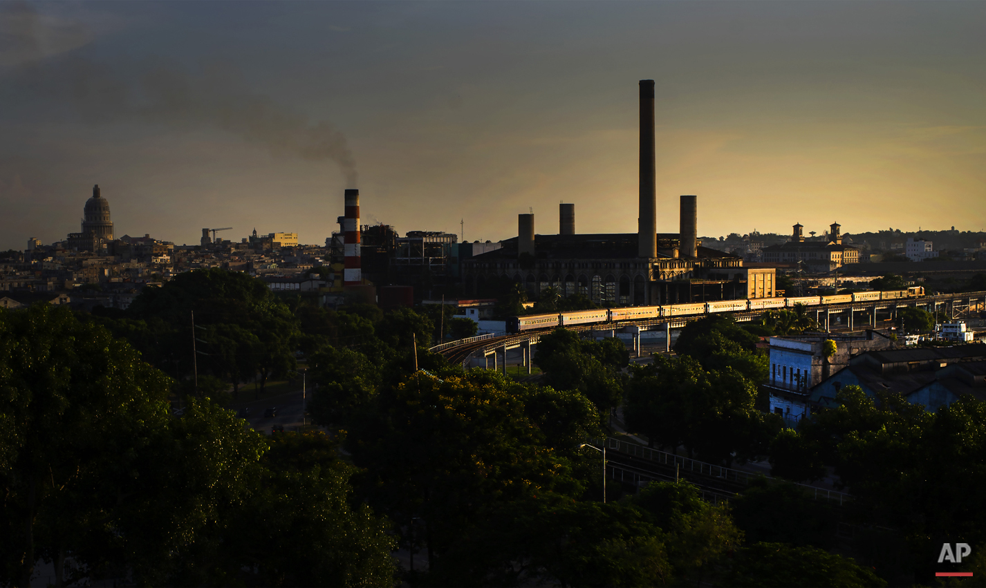 In this Aug. 28, 2015  photo, a train that departed Santiago de Cuba arrives at sunrise to Havana, Cuba. Cubans pay a little more than $1 to shuttle goods or visit faraway family, between the capital and Santiago. Visiting foreigners are charged $30 for the same trip. (AP Photo/Ramon Espinosa)