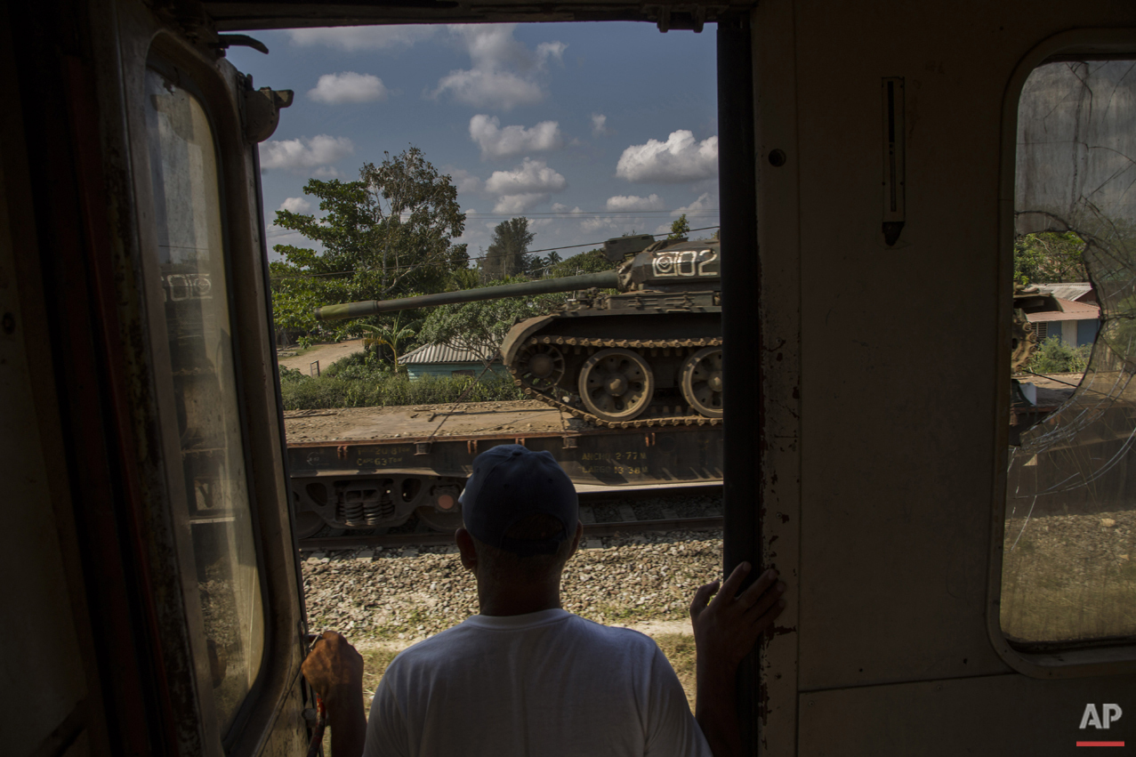 In this March 23, 2015 photo, a man looks at a tank being transported on a paused cargo train, as he travels by train through the province of Holguin, Cuba. The train system suffered along with much of the country's infrastructure when the Soviet Union's collapse cut Cuba off from the subsidies that Moscow had pumped into its economy. Currently, a longstanding U.S. trade embargo makes it hard to get parts. (AP Photo/Ramon Espinosa)