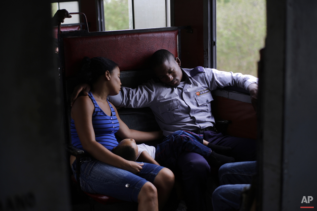 In this March 23, 2015 photo, an off-duty police officer travels with his family to Santa Clara during a long trip through the province of Holguin in Cuba. From east to the west, trains offer a fine-grained, slow-moving view of Cuba that few foreigners ever see. (AP Photo/Ramon Espinosa)